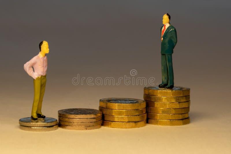 Obsługuje patrzeć biznesowego mężczyzny pozycja na górze wzrastać stosy złociste monety Biznesowy kariery pojęcie obraz stock