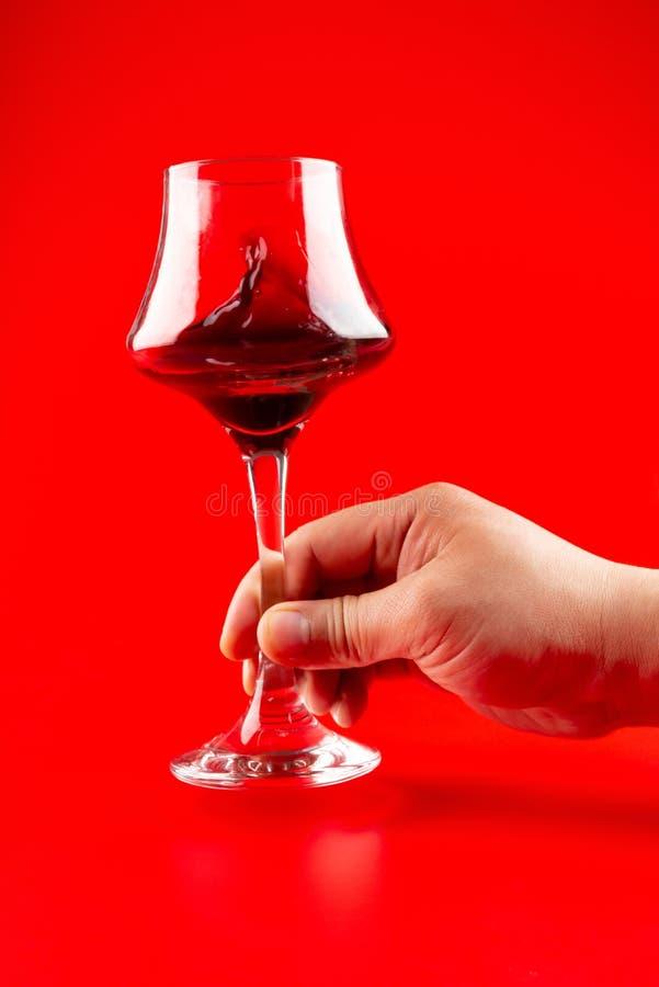 Obsługuje potrząsalną filiżankę czerwone wino na czerwonym tle obrazy royalty free