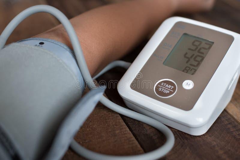 Obsługuje sprawdzać jego ciśnienie krwi używać elektronicznego ciśnienie krwi monitoru, sphygmomanometer na drewnianym stole lub fotografia stock