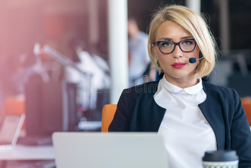 Obsługa klienta przedstawiciel przy pracą Piękna młoda kobieta w słuchawki pracuje przy komputerem obrazy stock