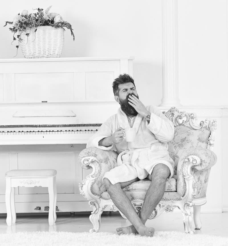 Obsługuje śpiącego w bathrobe, ziewanie, napoje kawowi w luksusowym hotelu w ranku, biały tło Elita czasu wolnego pojęcie człowie fotografia royalty free