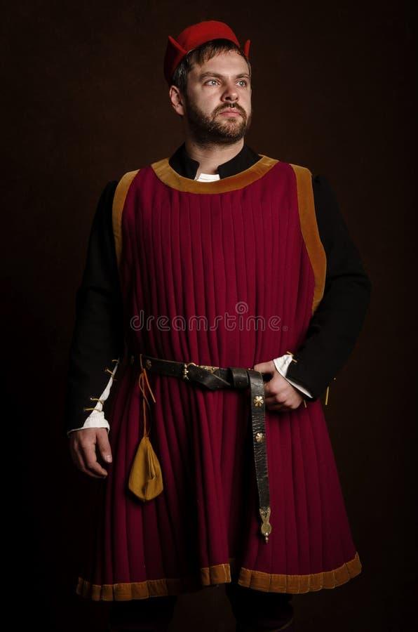 Obsługuje aktora w 15 wiek kostiumowy średniowiecznym na starzejącym się stylizowanym tle Hobby, odbudowa średniowieczny ży zdjęcie stock