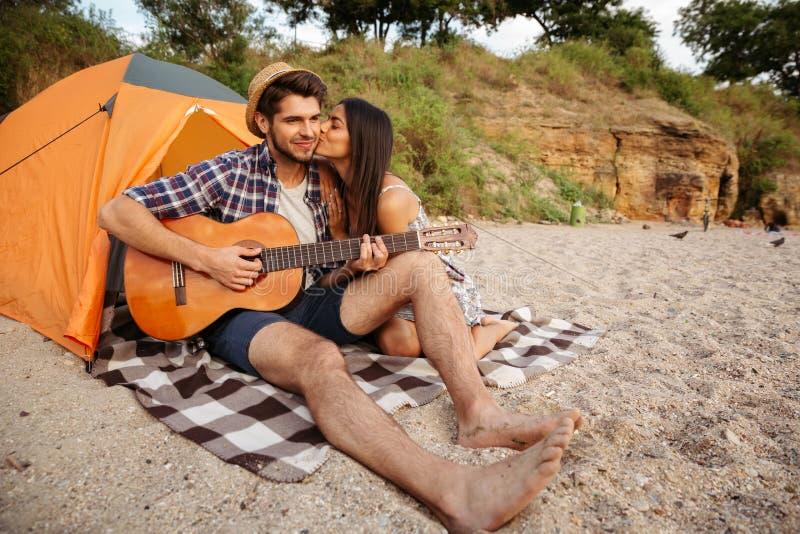 Obsługuje bawić się gitarę dla jego dziewczyny obsiadania przy namiotem zdjęcia royalty free