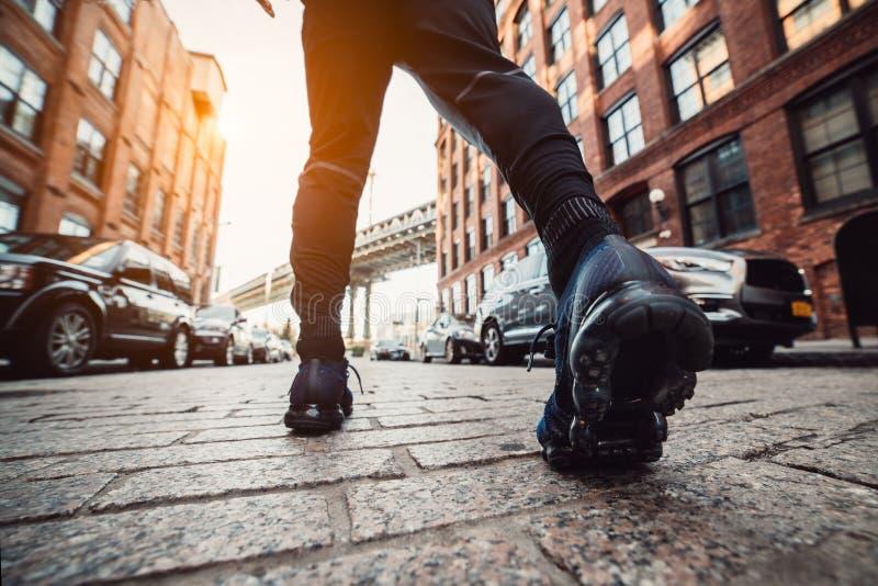 Obsługuje bieg przy Miasto Nowy Jork ulicą przy zmierzchu czasem Mężczyzn cieki z sportów sneakers outdoors zdjęcie stock