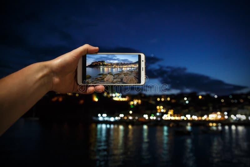 Obsługuje brać fotografię na telefonu komórkowego smartphone przy wieczór morza miastem obraz royalty free