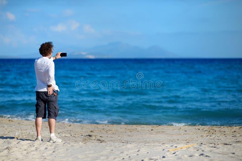 Obsługuje brać fotografię z telefonem komórkowym na plaży zdjęcie royalty free