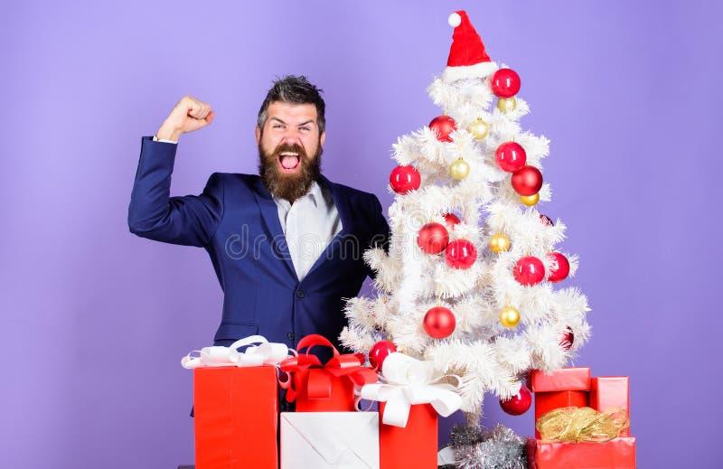 Obsługuje brodatej modniś odzieży formalnego kostium blisko choinki Bożenarodzeniowi prezenty i dekoracje Dlaczego organizować ws fotografia stock