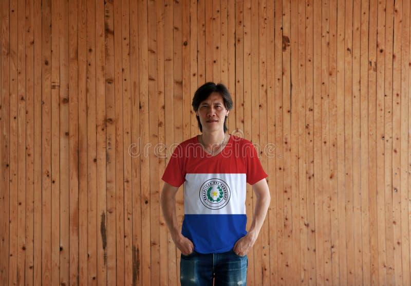 Obsługuje być ubranym Paraguay flagi koloru koszula i pozycja z dwa rękami wewnątrz dyszy kieszenie na drewnianym ściennym tle obraz royalty free