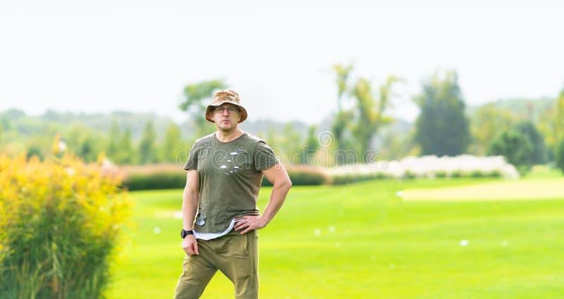 Obsługuje być ubranym zieloną koszulową pozycję w trawiastym polu zdjęcie stock