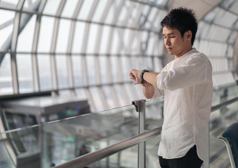 Obsługuje czekać na lot i przyglądającego mądrze zegarek w lotnisku obrazy royalty free