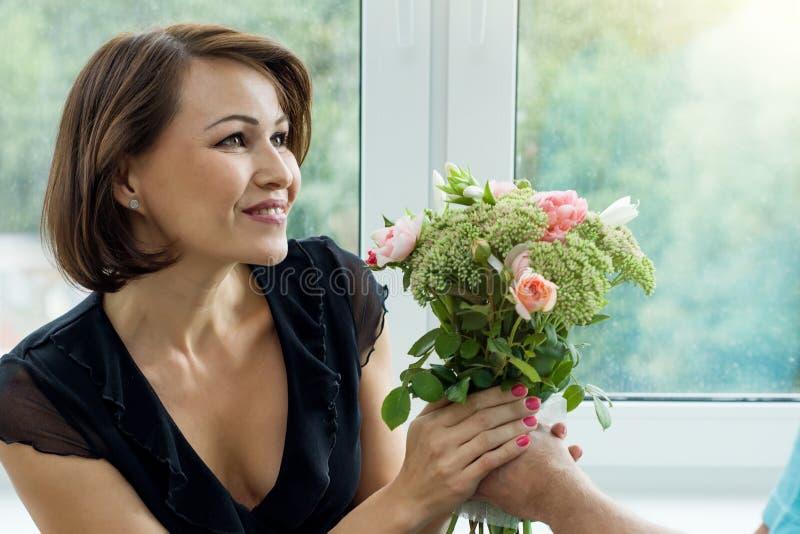 Obsługuje dawać bukietowi kwiaty i zdziwiona kobieta zdjęcia royalty free