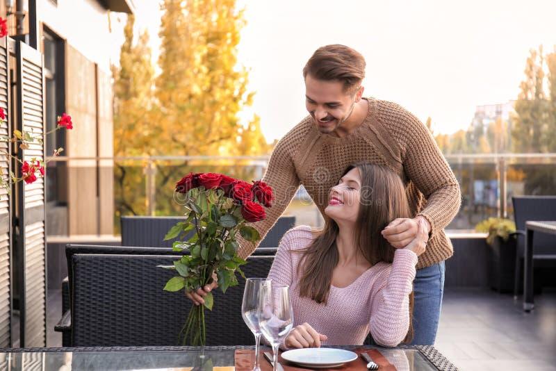 Obsługuje dawać róże jego dziewczyna na romantycznej dacie w kawiarni obraz royalty free