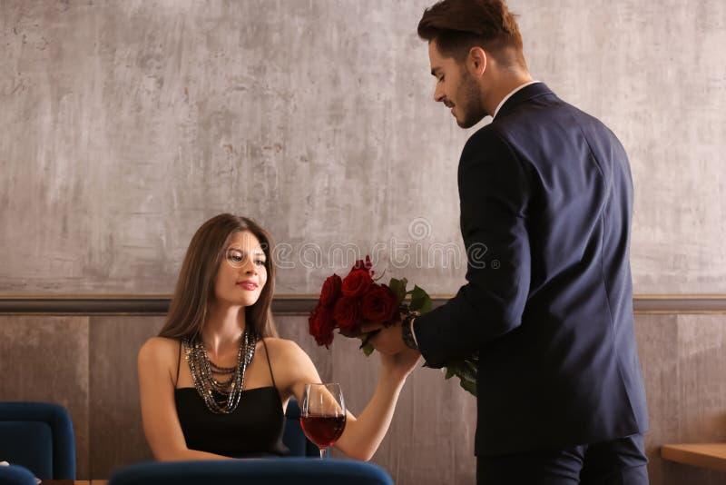 Obsługuje dawać róże jego dziewczyna na romantycznej dacie w restauracji fotografia royalty free