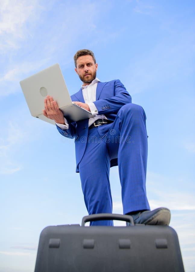 Obsługuje dobrze przygotowywającego biznesmena trzyma laptopu niebieskiego nieba tło Ufny przedsiębiorca Odgórnych ilości znakomi zdjęcie stock