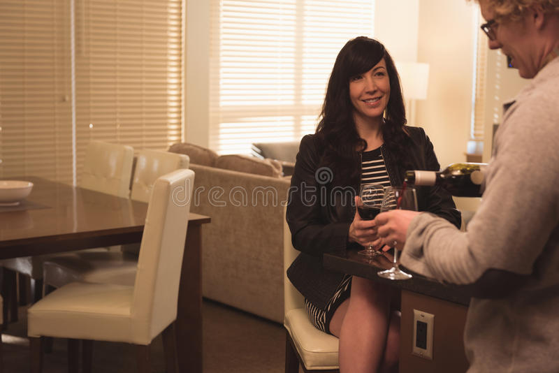 Obsługuje dolewania wino w wina szkło w domu zdjęcie stock