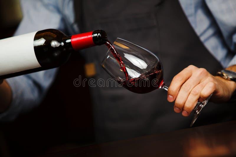 Obsługuje dolewania wino w wineglass, męska ręki mienia butelka fotografia stock