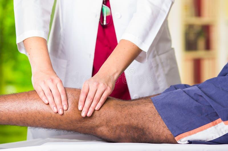 Obsługuje dostawać fizycznego nogi traktowanie od physio terapeuta, ona ręki pracuje na jego łydkach stosuje masaż, medycznego zdjęcia stock