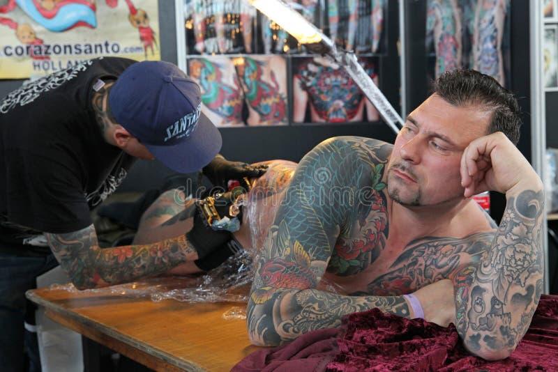 Obsługuje dostawać tatuaż, przy tatuażu studiiem zdjęcie royalty free
