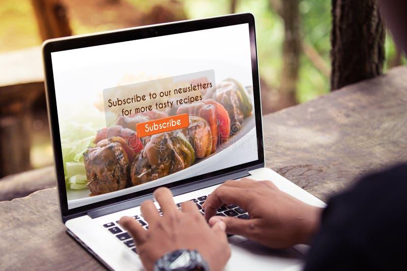 Obsługuje działanie na laptopie, komputerze robi/, prenumeruje karmowego blog na ekranie fotografia royalty free