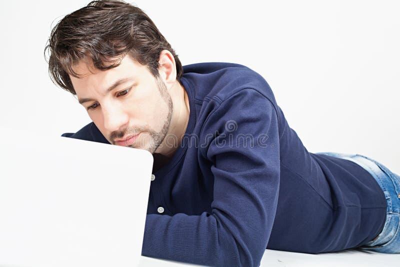 Obsługuje działanie na laptopie podczas gdy kłaść na podłoga zdjęcia stock