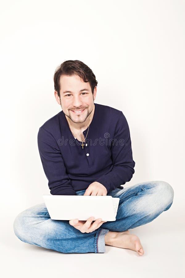 Obsługuje działanie na laptopie podczas gdy siedzący na podłoga obraz stock