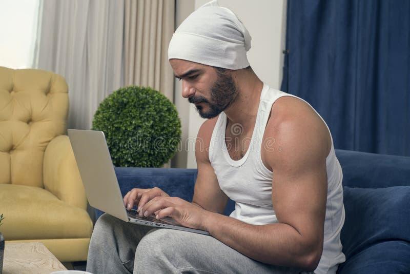 Obsługuje działanie na laptopie w domu, Przystojny facet pracuje na jego noteb obrazy royalty free