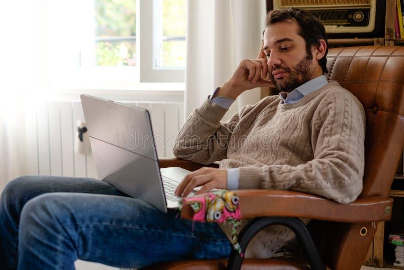Obsługuje działanie używa jego laptopu i fi interneta connecti w domu zdjęcie stock