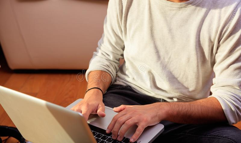 Obsługuje działanie z laptopu obsiadaniem na podłoga w domu zdjęcia royalty free