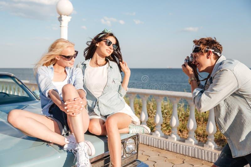 Obsługuje fotografa bierze fotografie dwa kobiety siedzi na samochodzie zdjęcia royalty free