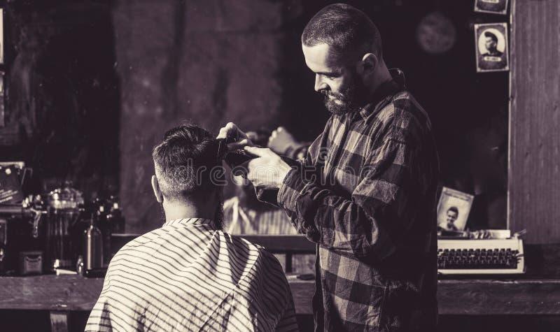 Obsługuje hairstylist fryzjera tnącego włosy męski klient Hairstylist porci klient przy fryzjera m?skiego sklepem M??czyzny odwie zdjęcia royalty free