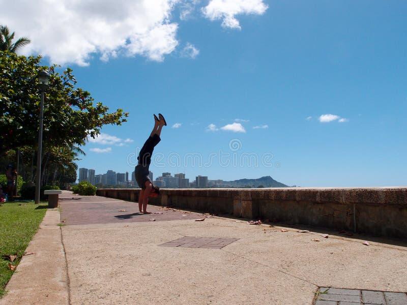 Obsługuje Handstands wzdłuż droga przemian Kewalo basenu park obrazy stock