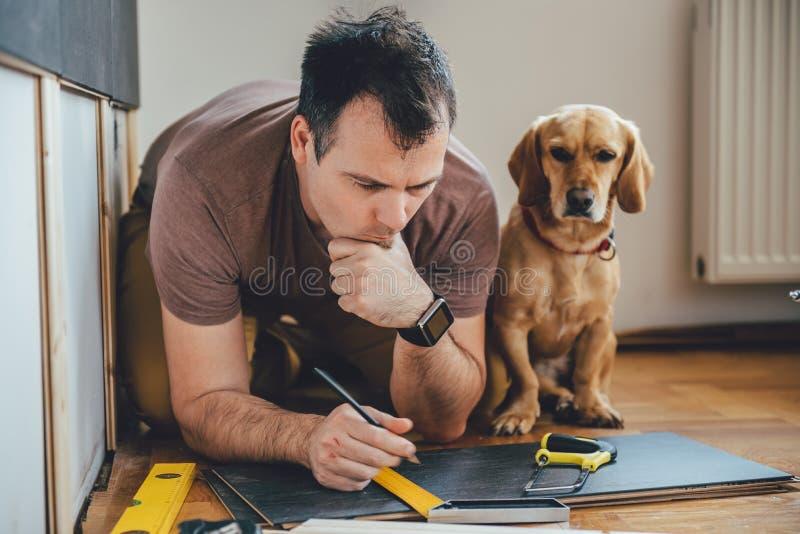 Obsługuje i jego pies robi odświeżanie pracie w domu zdjęcia stock