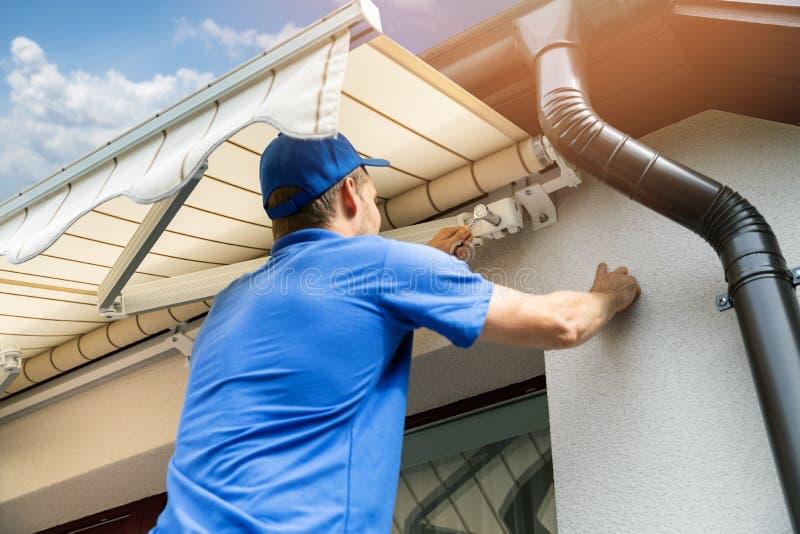 Obsługuje instalować markizę na domowej fasady ścianie nad balkonem zdjęcie stock