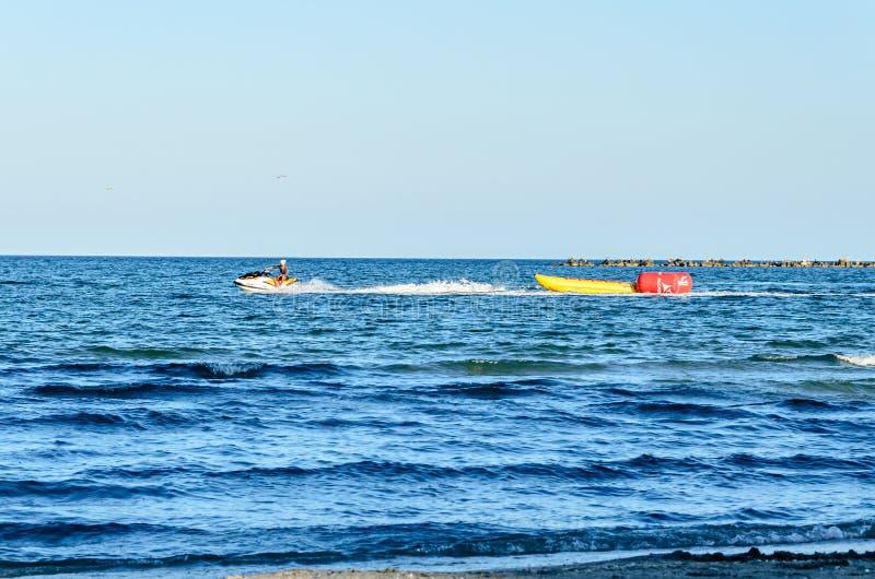 Obsługuje jechać dżetową nartę nad błękitnego czerni wodą morską, bananowa łódź obrazy royalty free