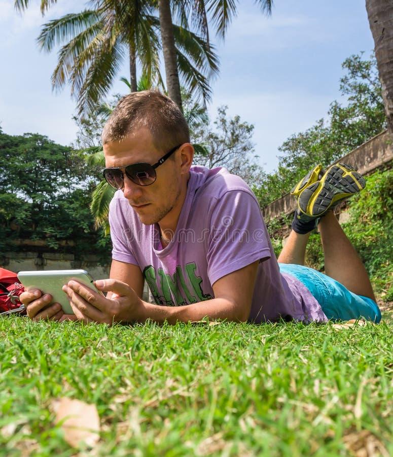 Obsługuje kłaść na trawie i używać jego pastylkę zdjęcia stock