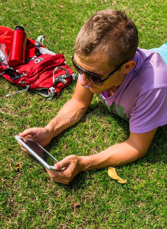 Obsługuje kłaść na trawie i używać jego pastylkę zdjęcia royalty free
