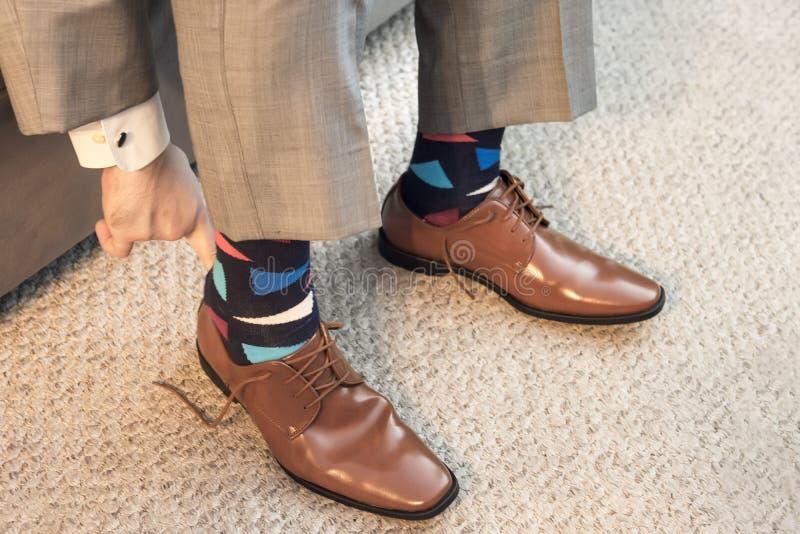 Obsługuje kładzenie na brown smokingowych butach w formalnej odzieży z kolorowymi skarpetami fotografia stock