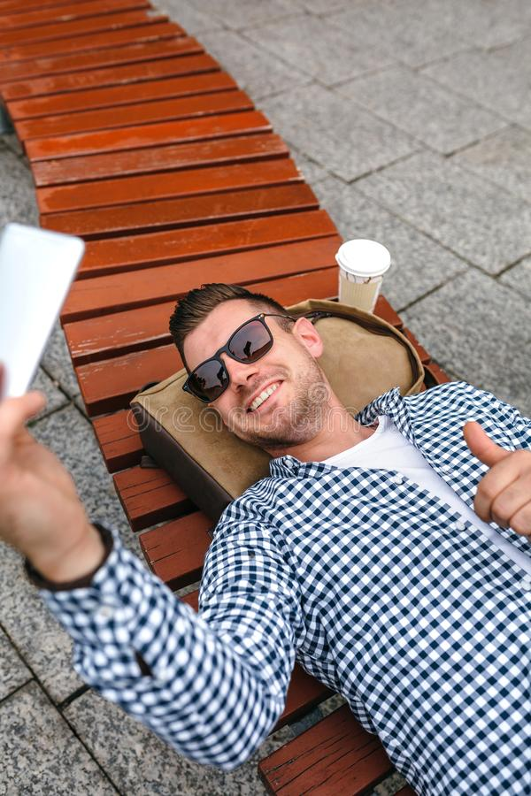 Obsługuje lying on the beach na parkowej ławce robi selfie z wiszącą ozdobą zdjęcie royalty free