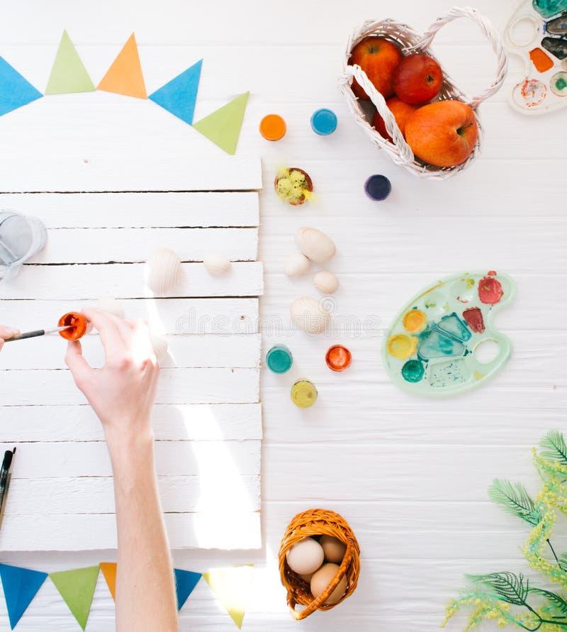 Obsługuje malować Wielkanocnych jajek życie na białym drewnianym tle wciąż obrazy royalty free