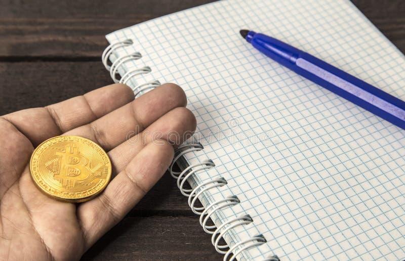 Obsługuje mienia bitcoin na jego ręce na drewnianym tle obraz royalty free