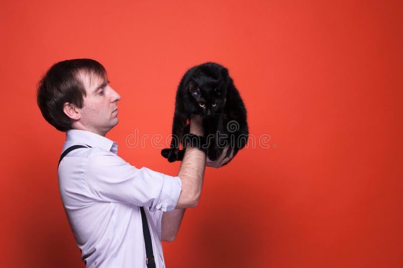 Obsługuje mienia i patrzeć ślicznego czarnego kota obrazy stock