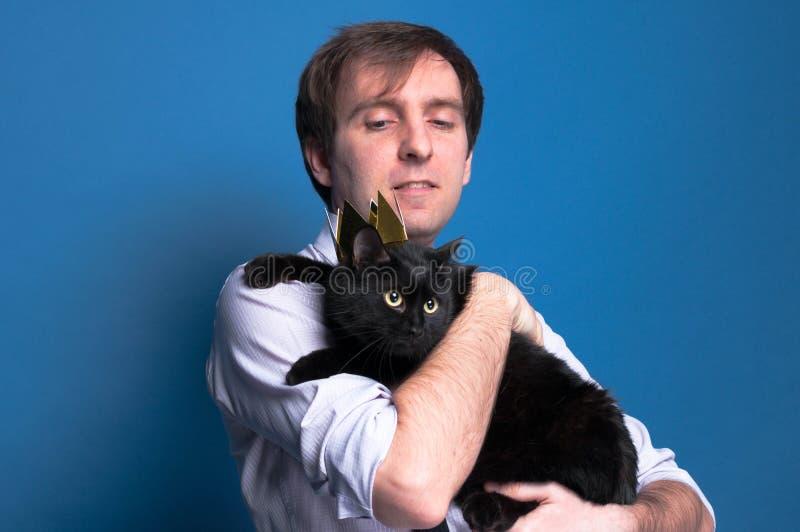 Obsługuje mienia i patrzeć śliczny czarny kot w złotej koronie zdjęcia royalty free
