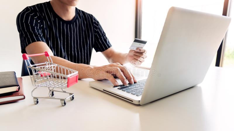 Obsługuje mienie kartę kredytową w ręce i wchodzić do ochrona kodzie używać mądrze telefon na laptop klawiaturze, online płatnicz fotografia stock