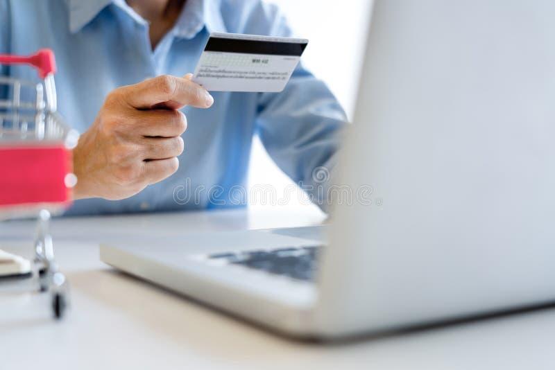 Obsługuje mienie kartę kredytową w ręce i wchodzić do ochrona kodzie używać mądrze telefon na laptop klawiaturze, online płatnicz zdjęcia royalty free