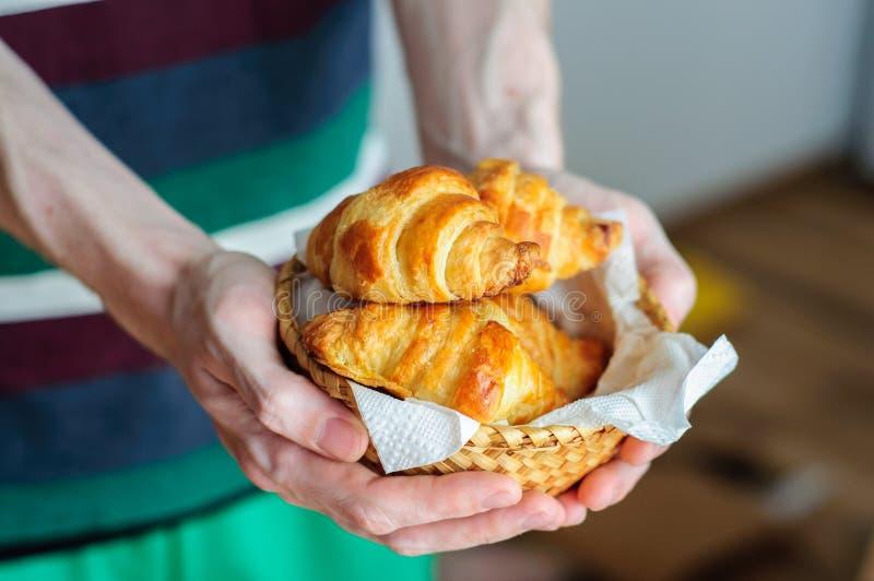 Obsługuje mienie słomianego kosz z świeżymi piec croissants fotografia royalty free