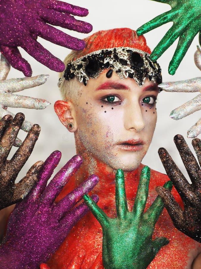 Obsługuje modela przy sztuka makijażem z zielonymi oczami chuje od kolorowych ręk zdjęcie royalty free
