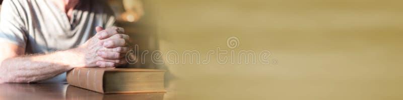 Obsługuje modlenie z jego rękami nad biblią obraz royalty free