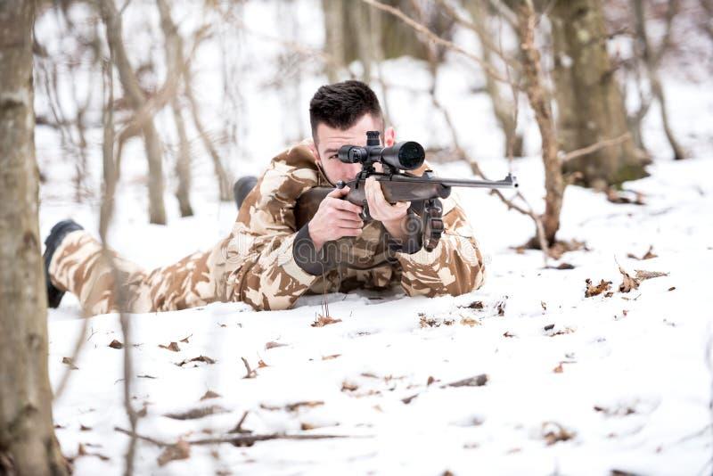 Obsługuje myśliwy strzelaninę z snajperskim karabinem, celowaniem i ostrzałów pociskami, fotografia stock