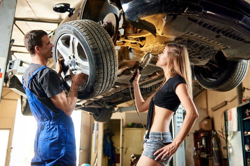 Obsługuje naprawianie samochód na hydraulicznym dźwignięciu, kobieta pomaga on obrazy stock