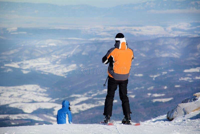 Obsługuje narciarki na skłonie w zimy górze obrazy royalty free